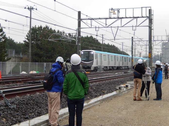 Crews oversee a train on powered tracks with linear motor reaction rails installed.