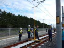 Crews make adjustments to the power supply and linear motor reaction rail.